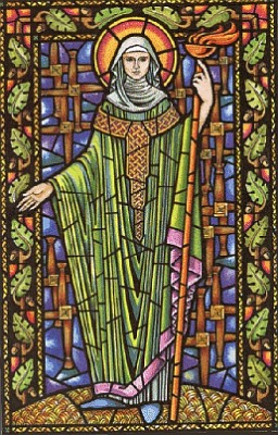 Stained glass window showing Brigit dressed in a green robe, standing and holding a staff.